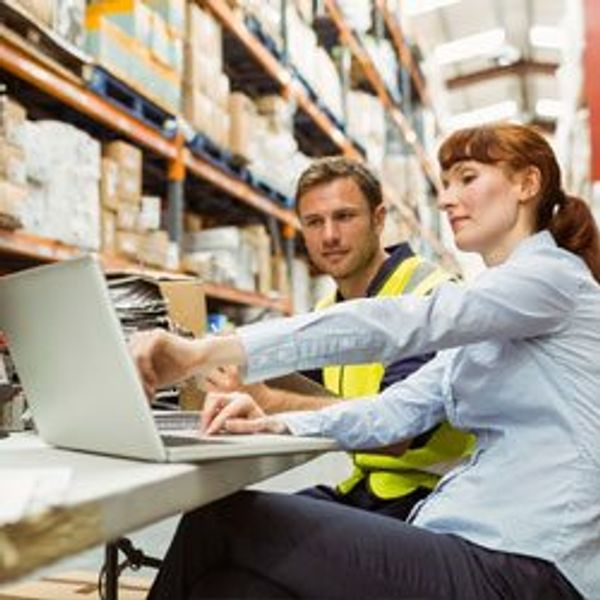 Two men looking at laptop in a warehouse