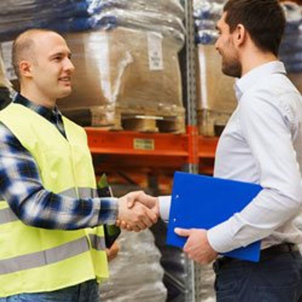 Men in warehouse shaking hands