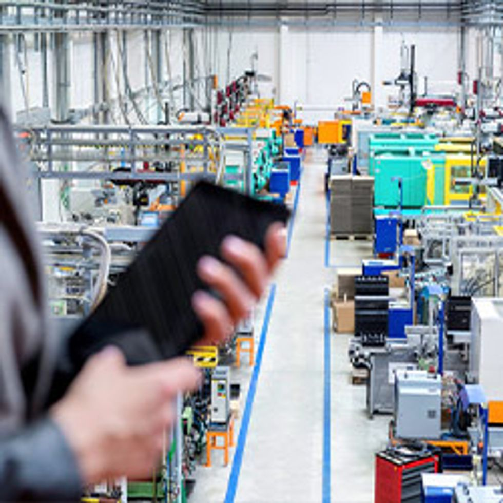 Businesswoman Checking in Factory on Tablet