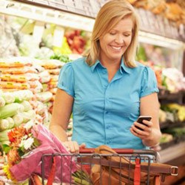 Woman grocery shopping with phone