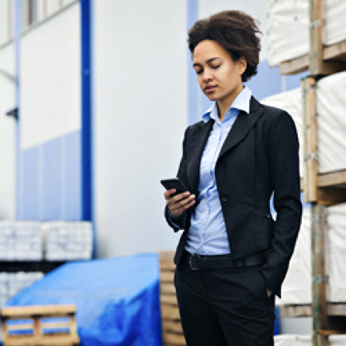 Woman looking at her phone in a warehouse environment